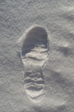 Bootprint in the Snow. A single human male bootprint as the start of a winter Christmas journey stock photo
