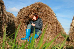 Boots. Child in a haystack - blue boots Stock Photography