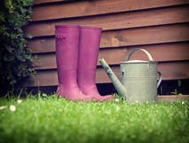 Boots. Pink boots with water can in garden Royalty Free Stock Image