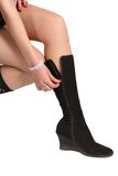 Boots. The girl clasps a fastener on a boot Royalty Free Stock Photo
