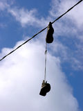 Boots. A pair of boots hanging from a power line on sky background Royalty Free Stock Photos