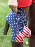 Boots in American Flag Style. Girl holds Boots in American Flag Style royalty free stock photo