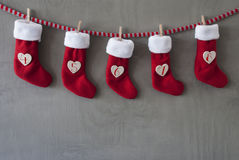 Boots As Advent Calendar, Cement, Nicholas Day. Nicholas Boots As Advent Calendar Hanging On A Line. Cement Wall As Modern Background. Textile Shoes With Hearts stock photo
