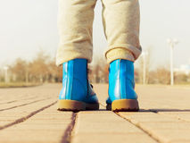 Boots of child walking at park Royalty Free Stock Images