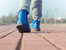 Boots of child walking at park Stock Image