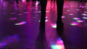 Boots dancing in disco. Woman in boots dancing on defocused dance floor background of a disco club with people dancing under blue and pink strobe lights stock video