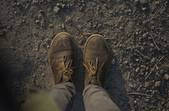 Dirty boots on a ground. Dusty military boots on the ground at sunset Royalty Free Stock Image