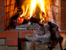 Boots are dried near fire in fireplace. In evening time stock photos