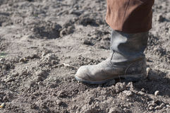Boots on dry earth. Royalty Free Stock Photography