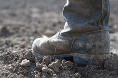 Boots on dry earth. Royalty Free Stock Image
