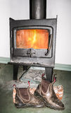 Boots drying in front of fire. Old work boots drying on log in front of lit metal combustion fireplace stock image