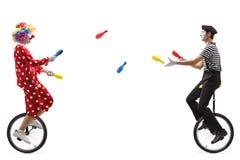 Boots en clown die op unicycles met clubs jongleren met na royalty-vrije stock foto's