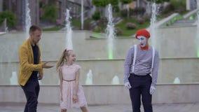 Boots en tovenaar die voor de meisjes` s aandacht vechten die haar hun vaardigheden tonen na stock videobeelden