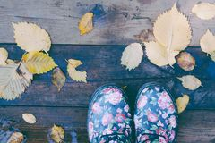Boots fall leaves wooden floor stock photography
