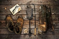 Boots, firewood and fireplace accessories - winter. Winter weekend in country cabin hut concept. Boots, book, firewood and fireplace accessories. Rustic layout Royalty Free Stock Photo