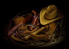 Boots and Gear. Cowboy gear with horse collar, lariat, six shooter, cowboy hat, boots, and spurs Royalty Free Stock Photo