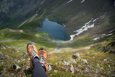 Boots & glacial lake in the mountains Royalty Free Stock Photography