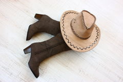 Boots and hat. Female boots khaki color and beige cowgirl hat on a floor Royalty Free Stock Images