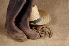 Boots, hat and Horseshoes 2. Muddy cowboy boots, straw hat and old horseshoes on a burlap background royalty free stock images