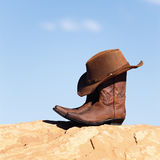 Boots and hat outdoor. Brown cowboy hat and boots outdoor royalty free stock photos
