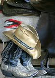 Boots, hat and saddle. Cowboy hat on boots with saddle and blanket in back ground Stock Photography