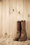 Boots on hay bale. Western style boots on hay with timber wall behind with copy space Royalty Free Stock Image