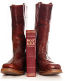 Boots and the Holly Bible. Against white background royalty free stock photos