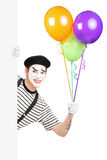 Boots kunstenaar na die een bos van ballons houden en van een paneel gluren Stock Foto's