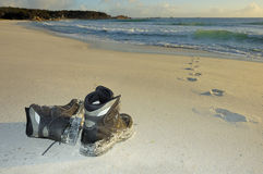 Boots left on the beach. A pair of boots on a sandy beach in the early light of dawn Footprints lead into the sea but do not come out again. Space for copy on Royalty Free Stock Image