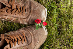 Boots in love. Two old boots in grass sharing love and two little red roses Stock Photography