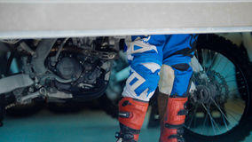 Boots of MXgirl in the garage with dirtbike. Telephoto Royalty Free Stock Image