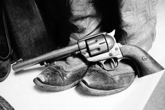 Boots and a pistol. A picture of some old cowboy boots with a pistol in black and white Royalty Free Stock Images