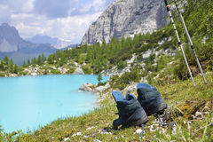 Boots and poles. A pair of boots and  ski-pole used for the outdoor trekking,on a beautiful landscape with a lake and mountains Stock Image
