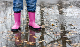 Boots in a puddle. Child standing in a puddle wearing a rubber boots Royalty Free Stock Photography