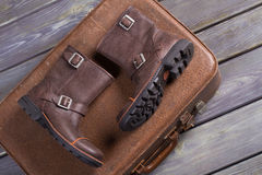 Boots on retro suitcase. Stylish men's boots lie on retro suitcase Royalty Free Stock Photos