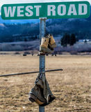 Boots On A Road Sign Royalty Free Stock Photos