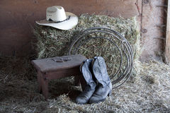 Boots, rope, and hat. Some boots, a hat, a rope, and a bale of hay royalty free stock image