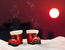 Boots Santa Claus. Boots Santa Claus standing on a roof and they smoke on the fast run Stock Photo