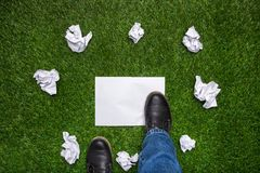 Boots on sheet of paper with cramled sheets on the grass Royalty Free Stock Images