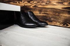 Boots and shoes box on wooden background Stock Photos
