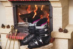 Boots ski boots in front of fireplace. Drying shoes in front of the fireplace. Two ski boots stand on a stool in front of a burning fireplace royalty free stock image