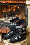 Boots ski boots in front of fireplace. Drying shoes in front of the fireplace. Two ski boots stand on a stool in front of a burning fireplace royalty free stock photography