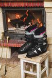 Boots ski boots in front of fireplace. Drying shoes in front of the fireplace. Two ski boots stand on a stool in front of a burning fireplace stock photography