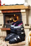Boots ski boots in front of fireplace. Drying shoes in front of the fireplace. Two ski boots stand on a stool in front of a burning fireplace in a bright room stock photography