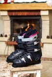 Boots ski boots in front of fireplace. Drying shoes in front of the fireplace. Two ski boots stand on a stool in front of a burning fireplace in a bright room royalty free stock photography