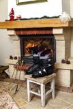 Boots ski boots in front of fireplace. Drying shoes in front of the fireplace. Two ski boots stand on a stool in front of a burning fireplace in a bright room royalty free stock image