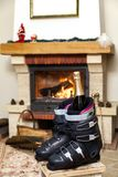 Boots ski boots in front of fireplace. Romance of downhill skiing. Two ski boots stand in front of a burning fireplace. In the left shoe there is a bottle of stock photography