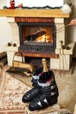 Boots ski boots in front of fireplace. Romance of downhill skiing. Two ski boots stand in front of a burning fireplace. In the left shoe there is a bottle of royalty free stock images