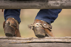 Boots and Spurs. Cowboy boots and spurs resting on a split rail fence Royalty Free Stock Photography