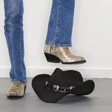 Boots stomping cowboy hat. Woman wearing snakeskin cowboy boots holding foot as if to stomp on black cowboy hat stock images